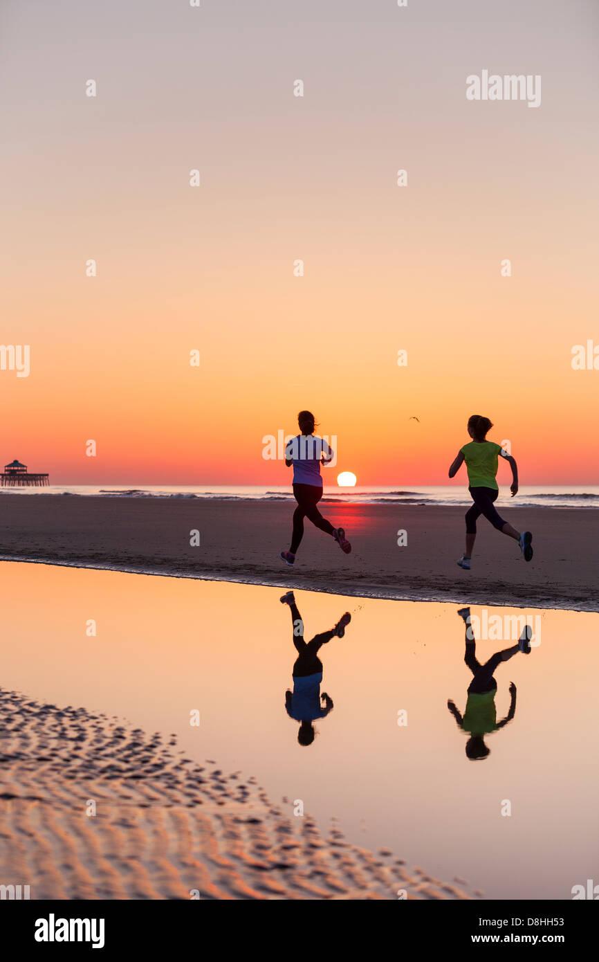 Zwei Jogger laufen am Strand Stockbild
