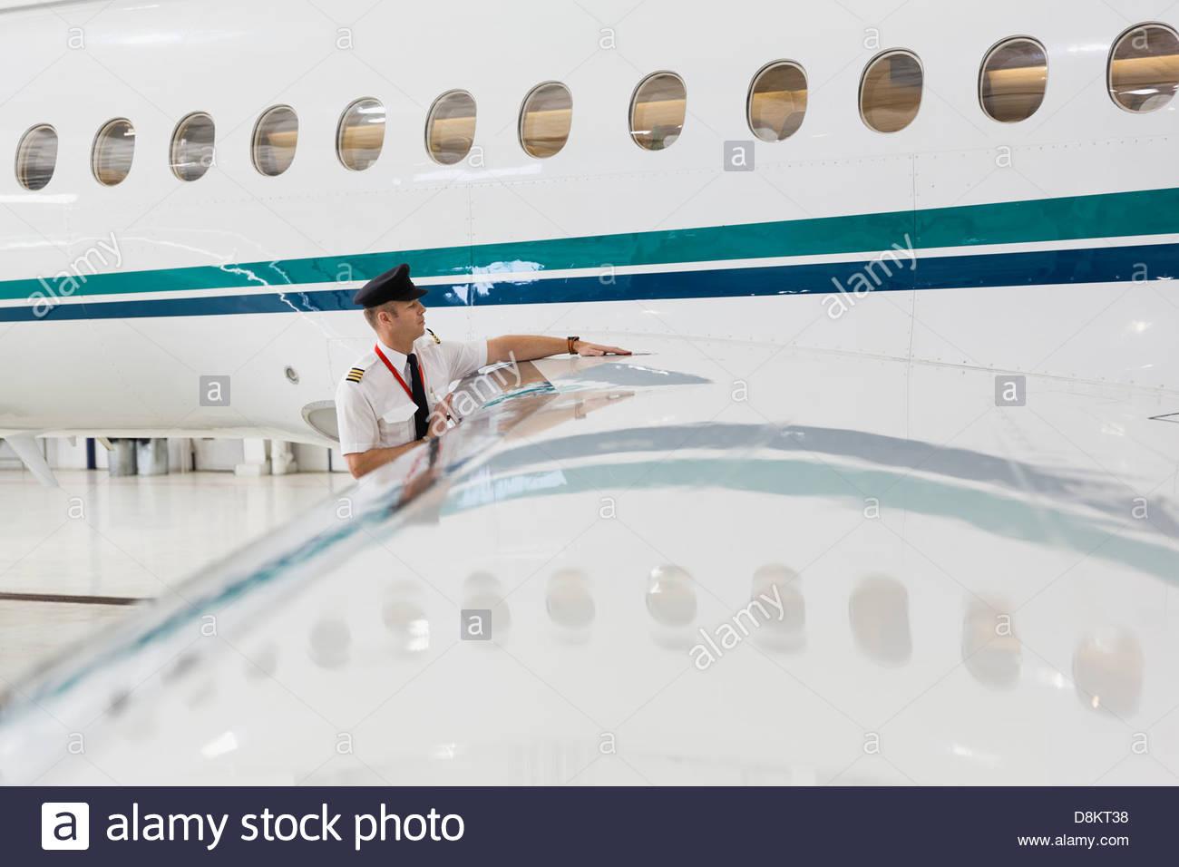 Männliche Piloten überprüfen Flugzeugflügel im hangar Stockbild