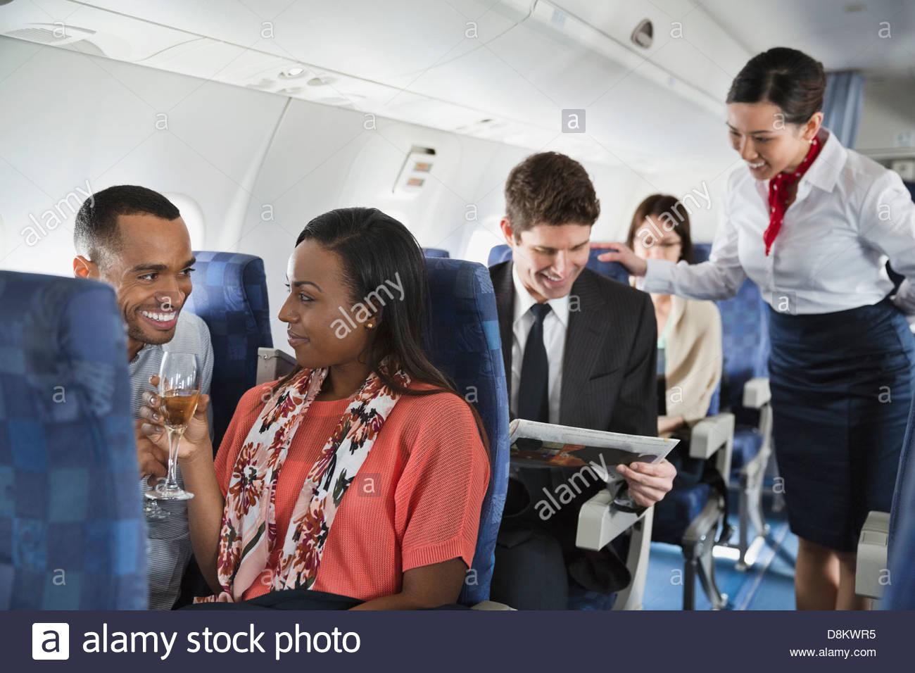 Paar entspannen bei einem Drink im Flugzeug Stockbild