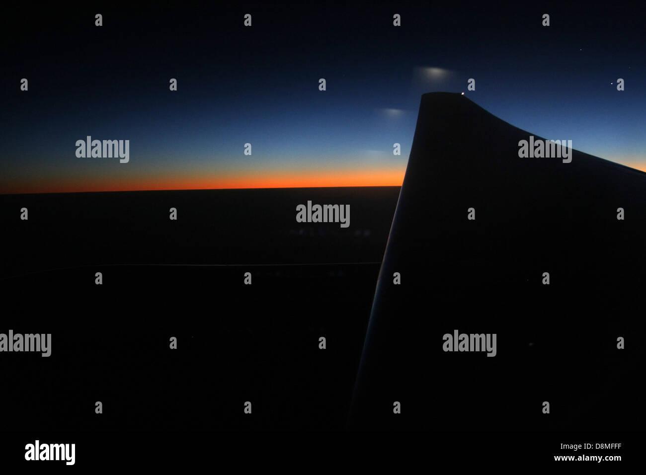 Blick bei Nacht aus einem Flugzeug Fenster, Sonnenuntergang und Flugzeug Flügelspitze Stockbild