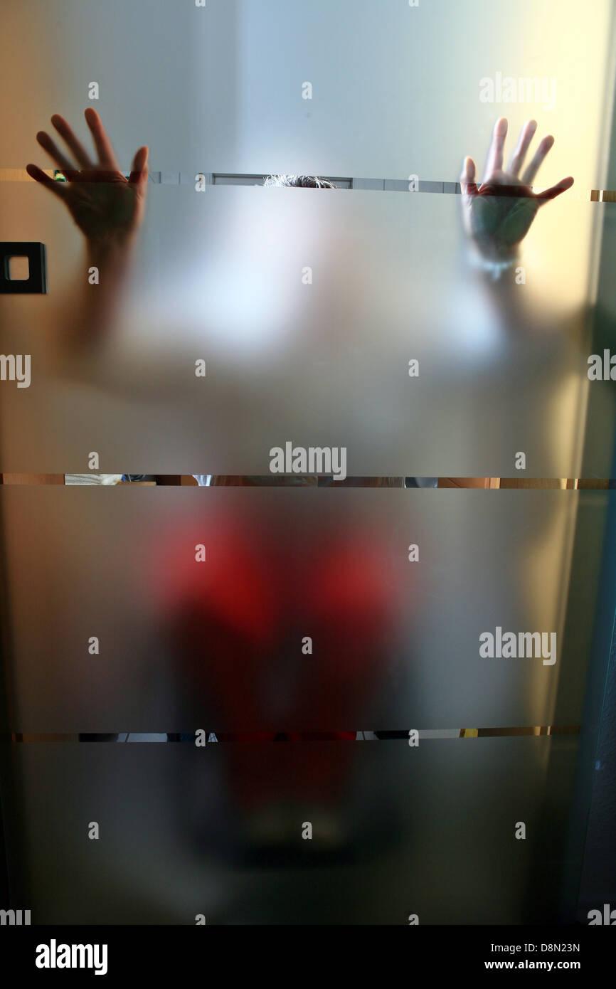 Frau in einem Rollstuhl hinter einer glasdoor Stockbild