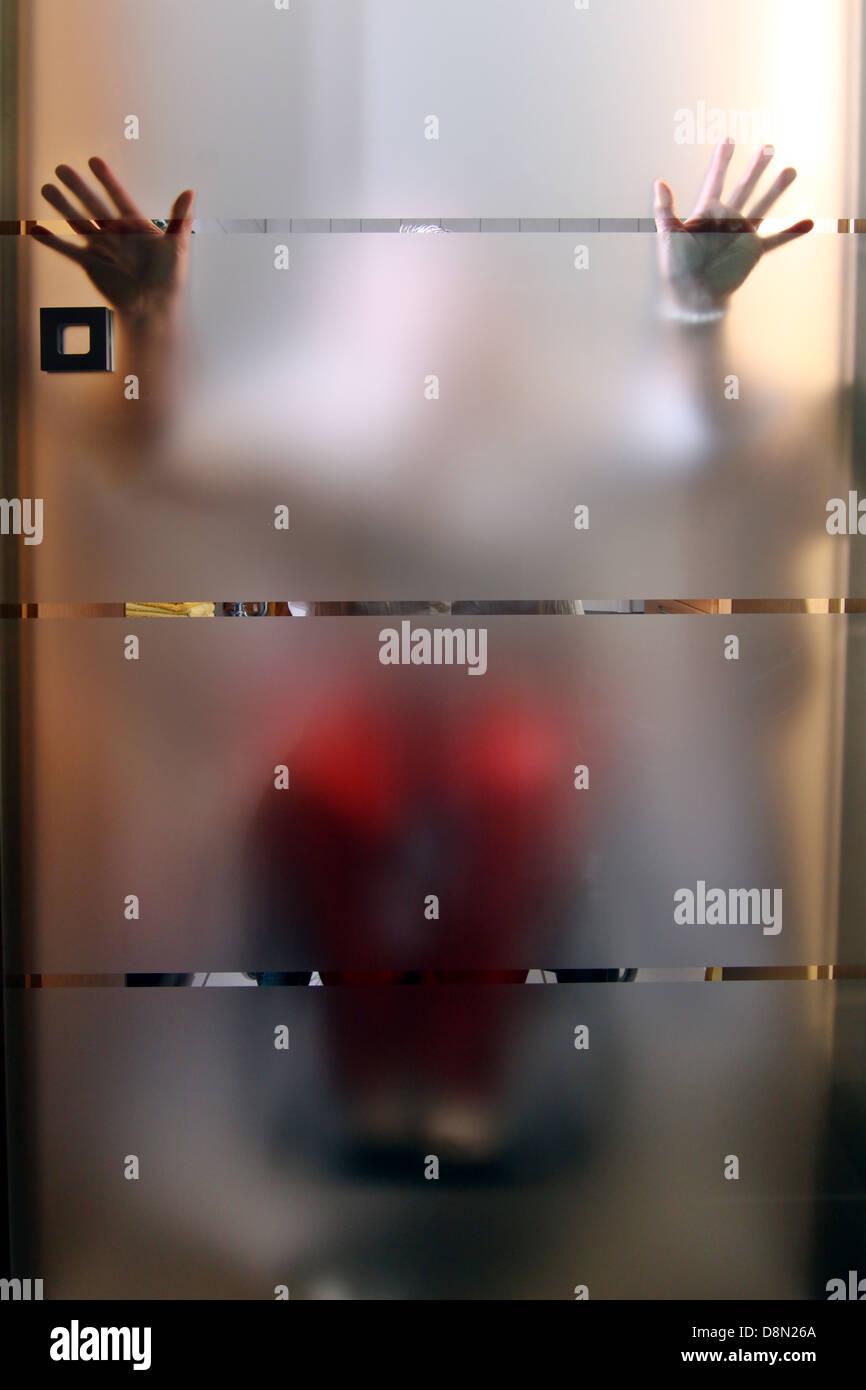 Frau in einem Rollstuhl hinter einer Glas-Tür Stockbild