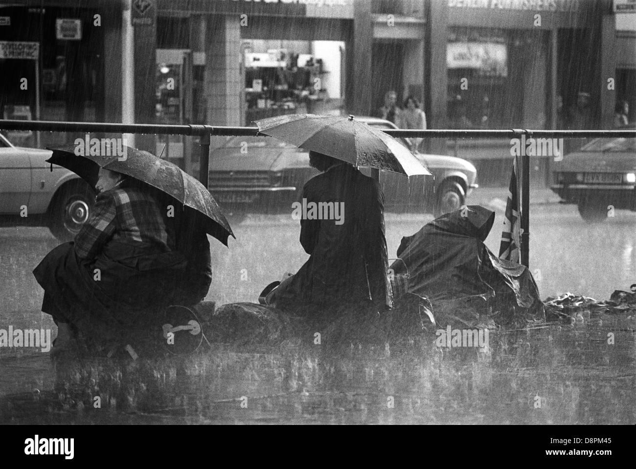 Schlechtes Wetter Queens Silver Jubilee 1977 Menschen sichern eine gute Position das Silberne Jubiläum Prozession Stockbild