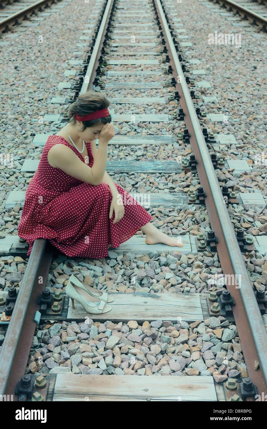 ein trauriges Mädchen auf Schienen Stockbild