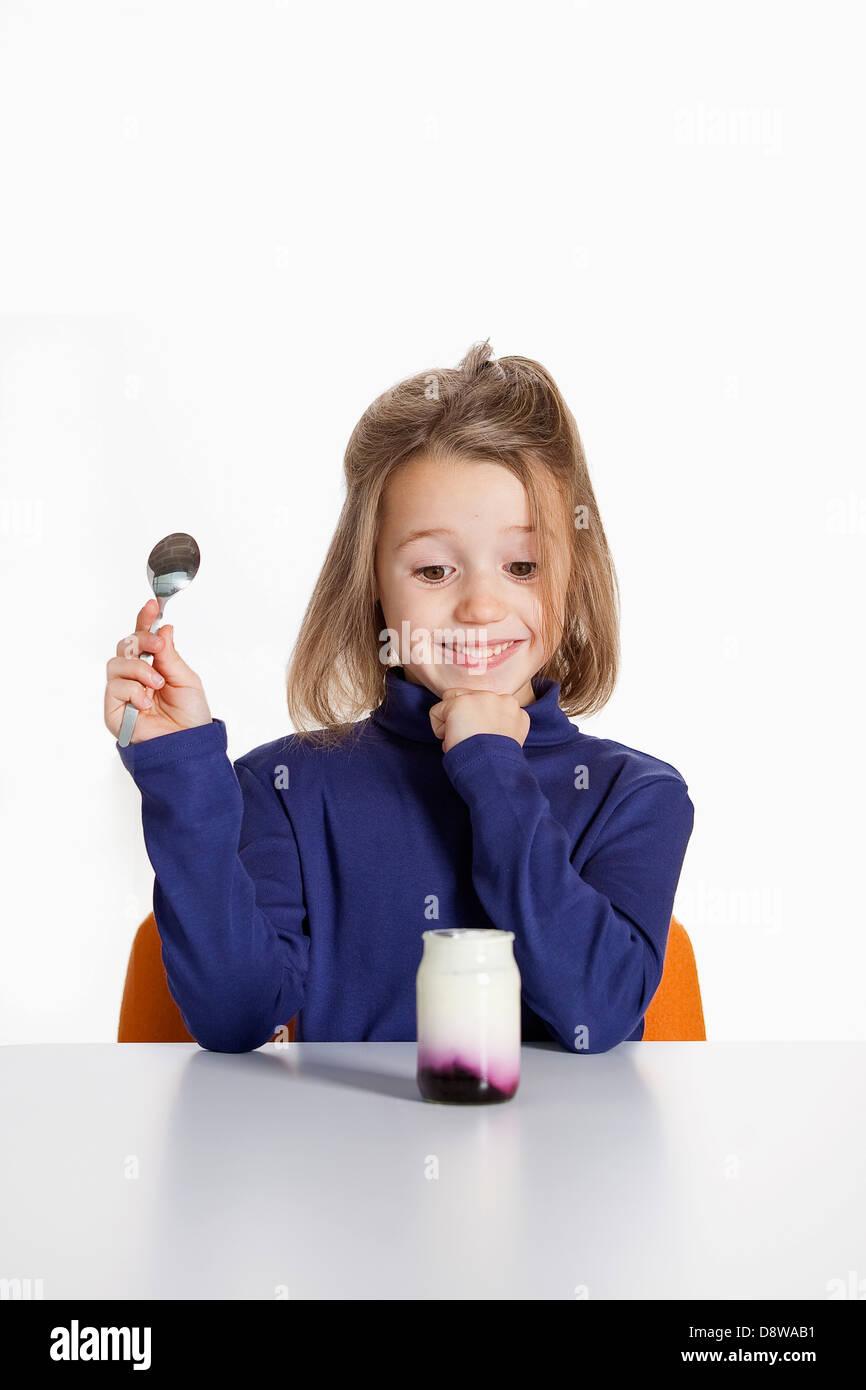 Pürieren Sie glückliches Mädchen essen ein Naturjoghurt mit blackberry Stockfoto