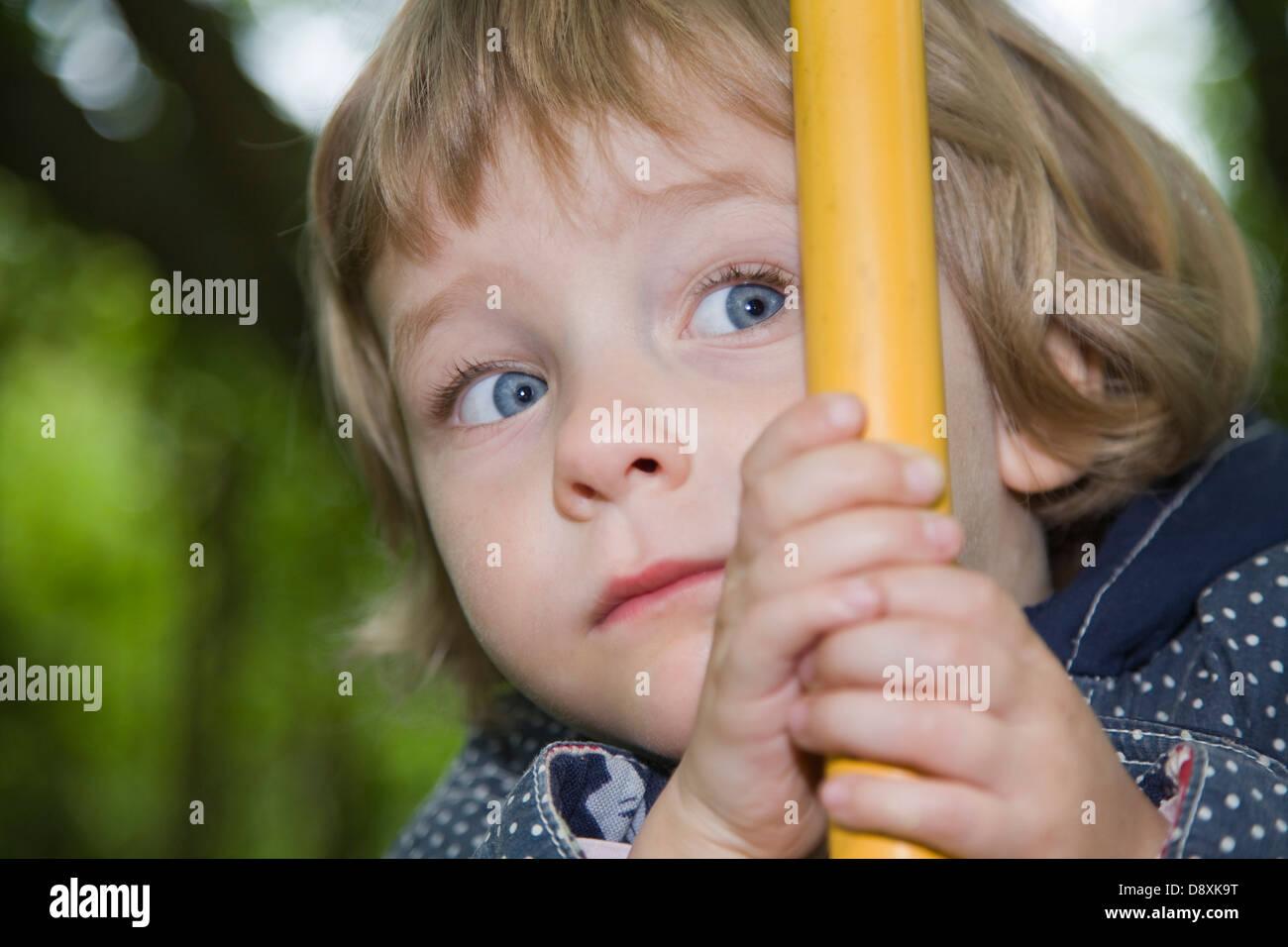 Drei-jährige Mädchen versteckt sich hinter einer bar Stockbild