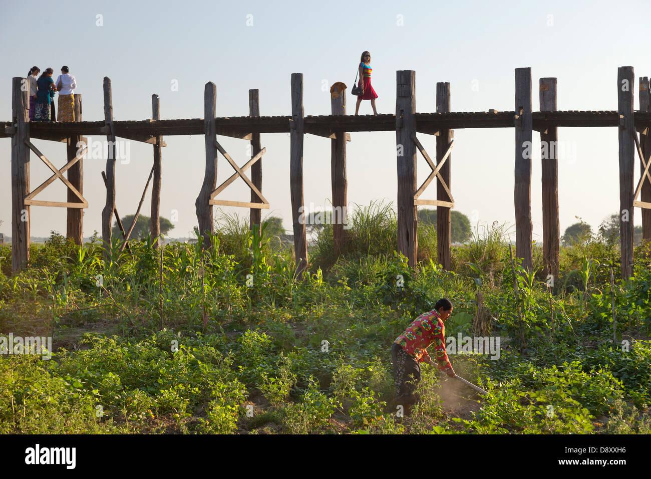 Gut gekleidete Frau Crossing U Bein Teakholz Brücke über den Taungthaman See, Myanmar, mit Landwirt schuften Stockbild