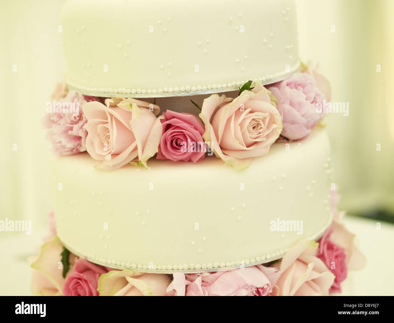 Eine zarte dreistufigen Hochzeitstorte mit Rosen dekoriert. Stockbild
