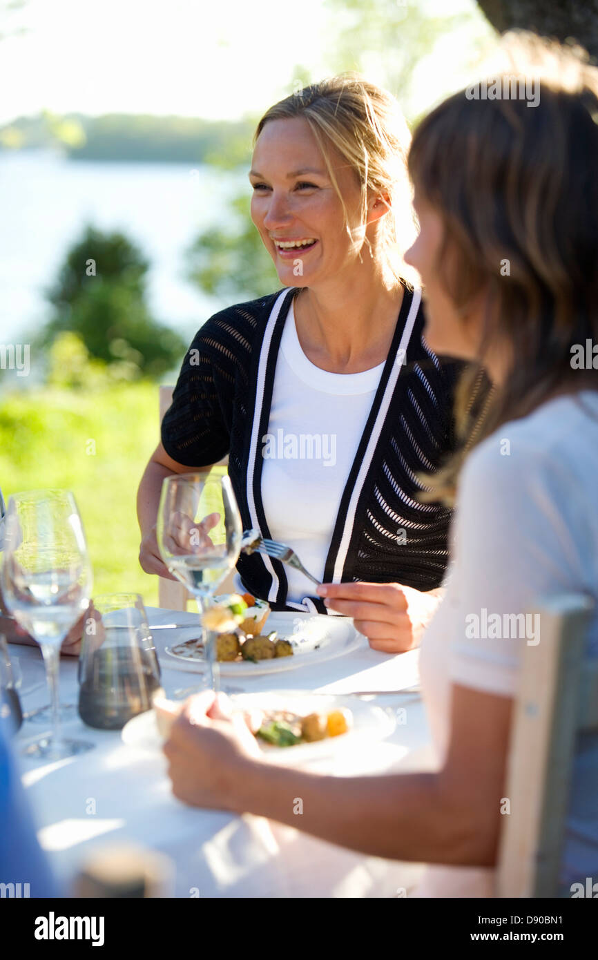 Zwei Frauen dem Mittagessen in einem Mittsommer Party, Fejan, Stockholmer Schären, Schweden. Stockfoto