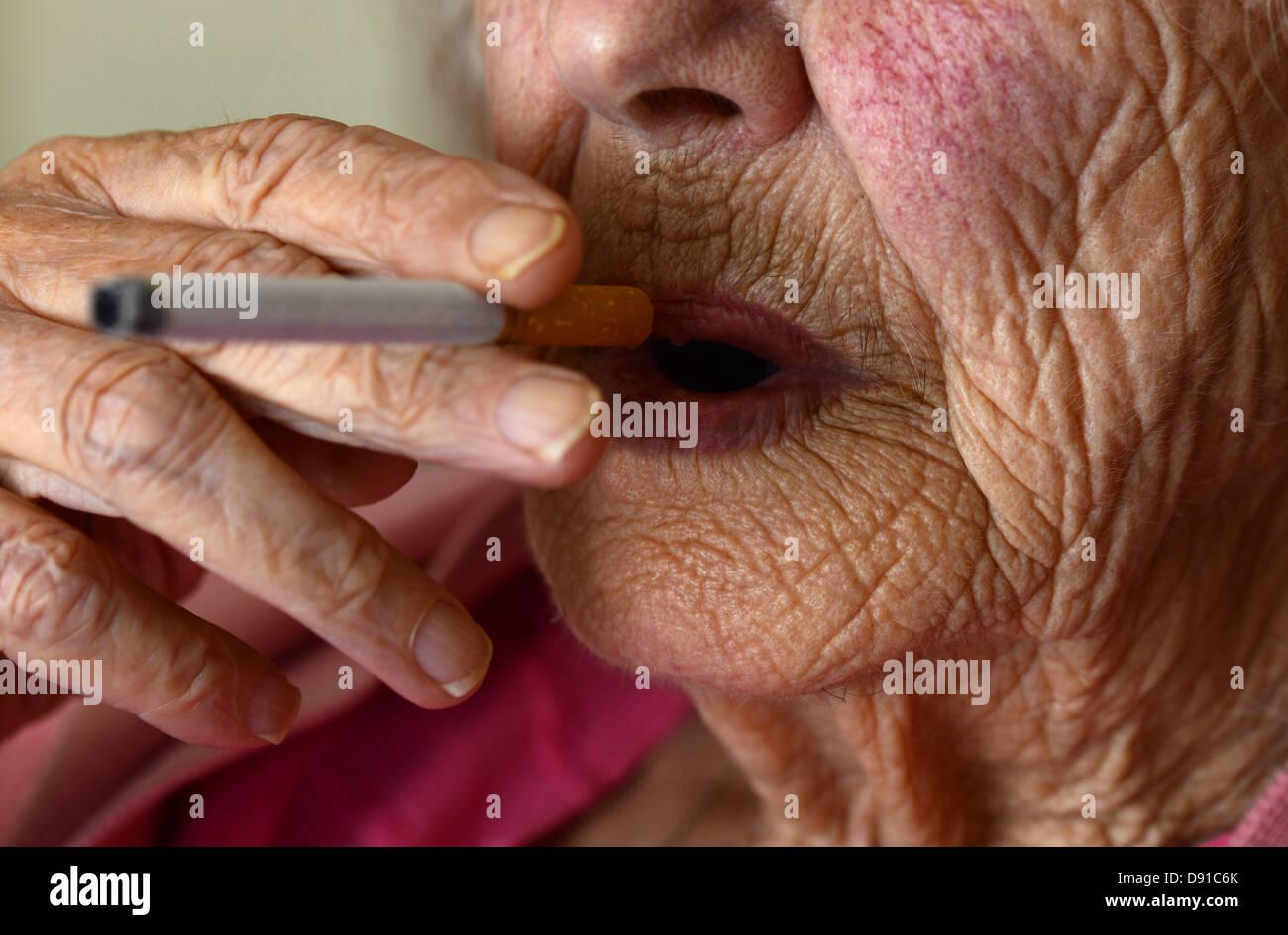 Alte Frau Rauchen, ältere Frau Raucher mit einer Zigarette, ältere Dame, die Rauchen Stockbild