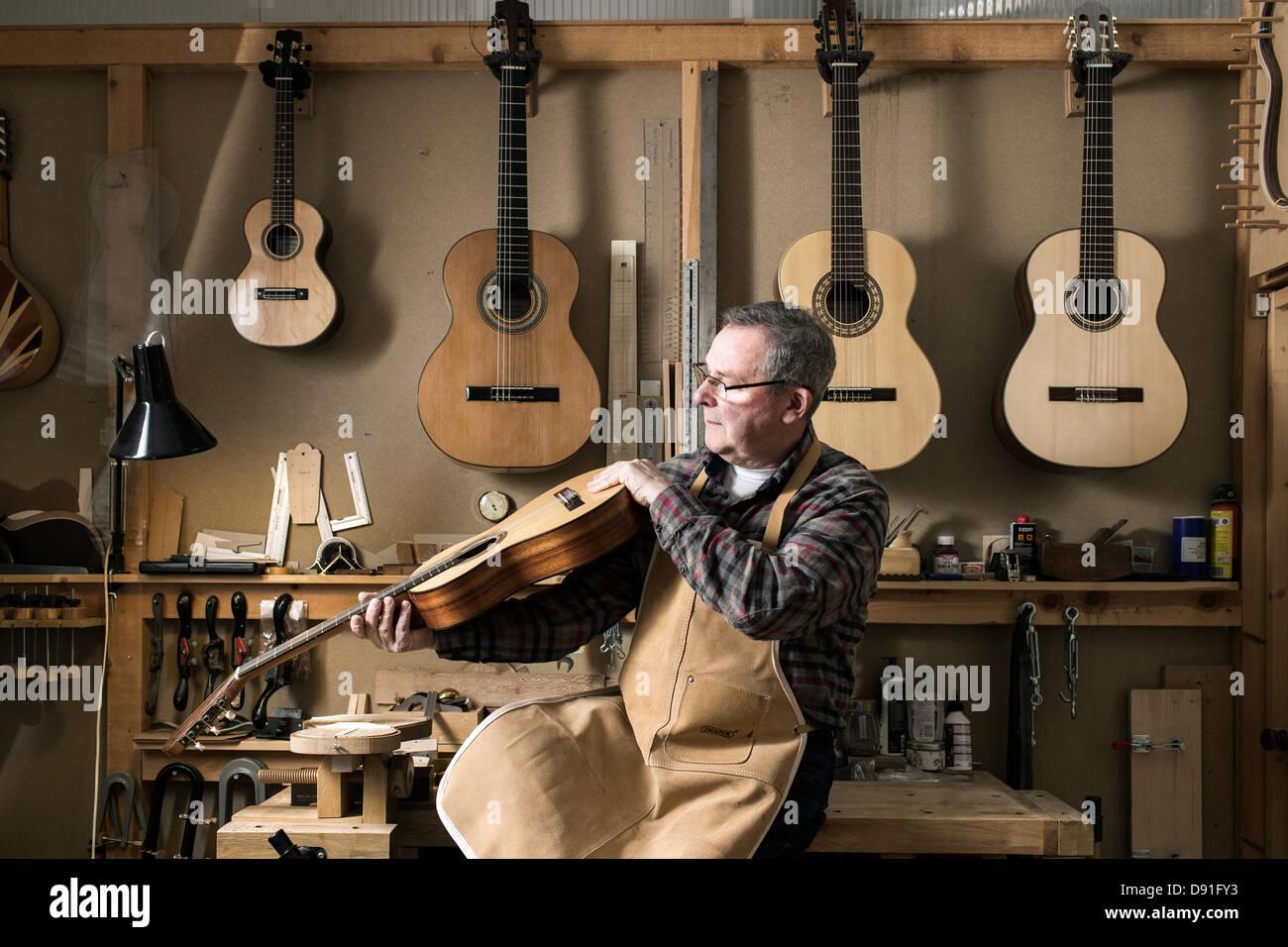 Gitarrenbauer Veredelung Akustikgitarre in Werkstatt Stockbild