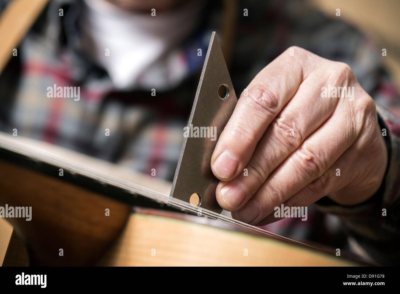 Nahaufnahme von Gitarrenbauer Veredelung Akustikgitarre in Werkstatt Stockbild
