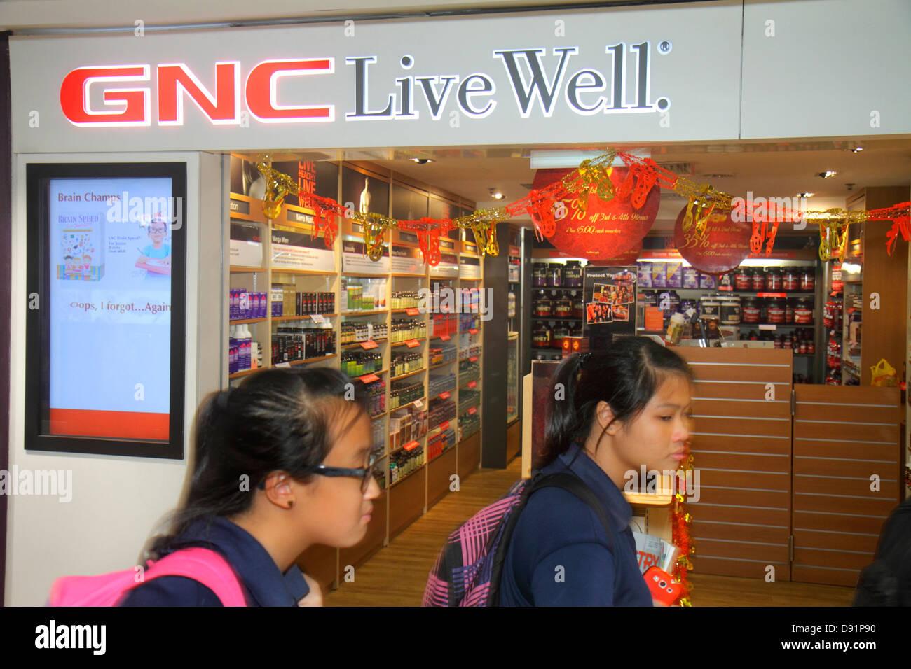 Singapur Bishan Ort Junction 8 Einkaufszentrum GNC Live Well Vitaminen front Eingang asiatische Studentin Stockbild