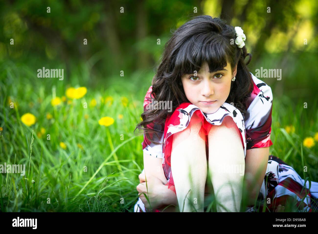 Porträt von einem Teen Mädchen sitzen auf der Wiese Stockbild