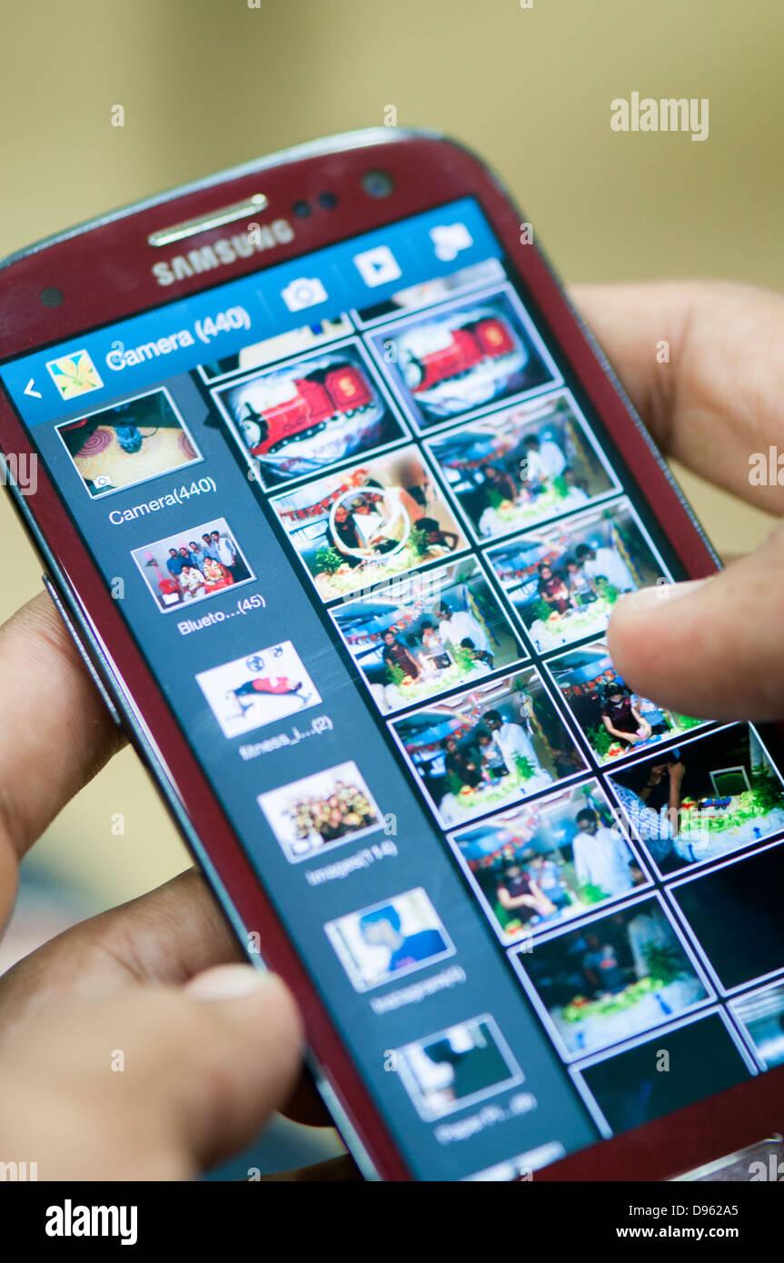 Anzeigen von Fotos in smartphone Stockbild