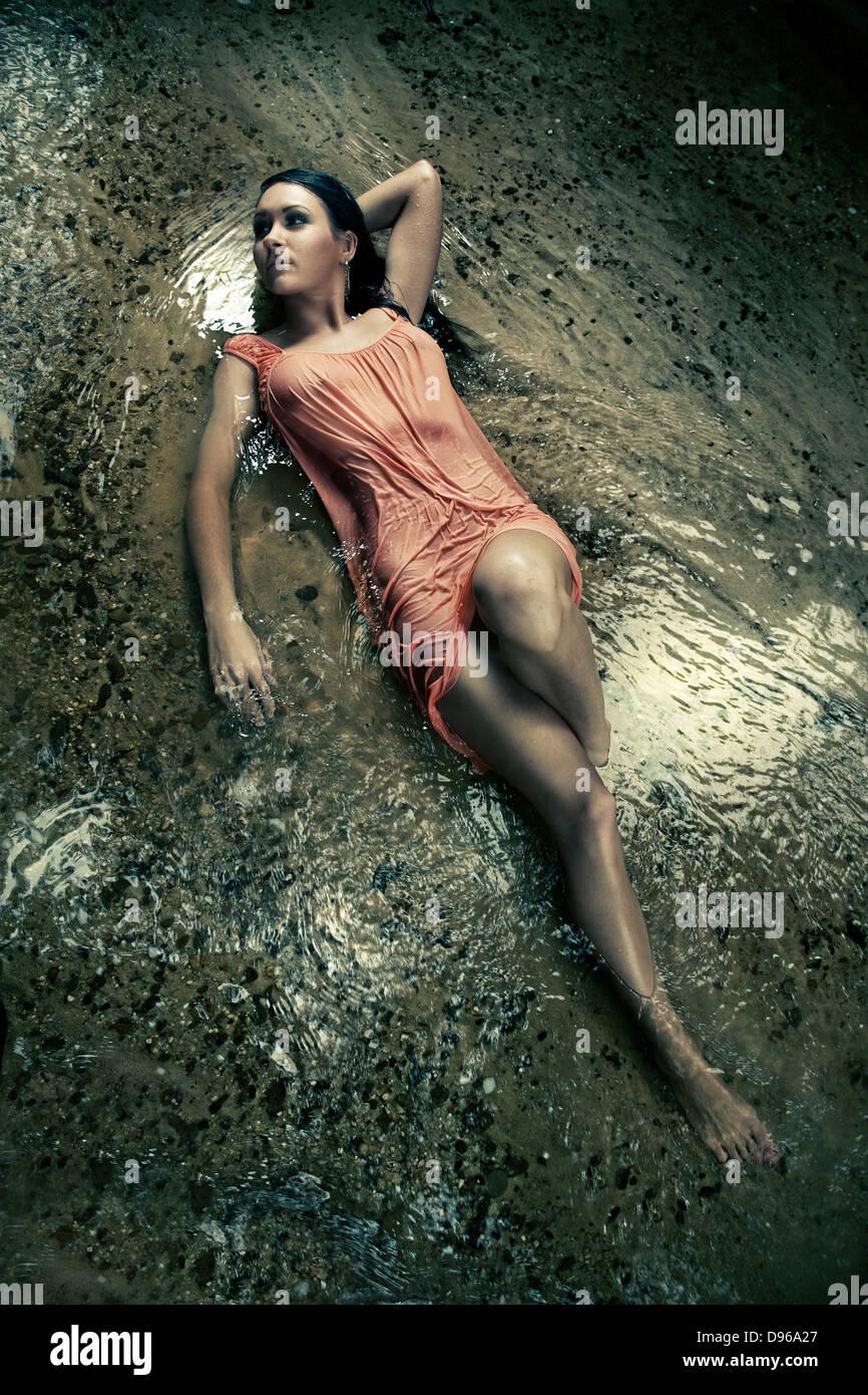 Frau im nassen Kleid im Bachbett Stockbild