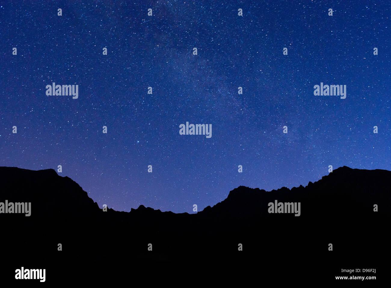Sterne und die Umrisse der Berge rings um den Cirque de Cilaos Caldera auf der französischen Insel La Réunion. Stockbild