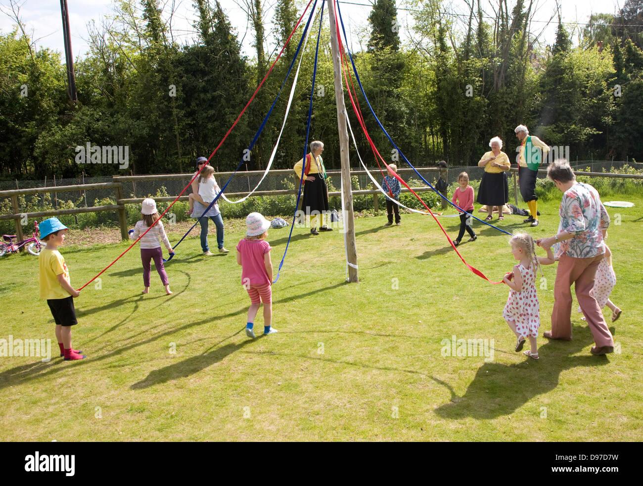 Kinder tanzen um einen Maibaum bei einem englischen Country Festival, Shottisham, Suffolk, England Stockbild