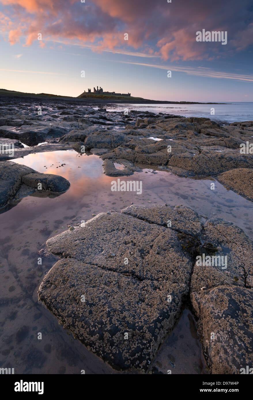 Sonnenuntergang über Dunstanburgh Castle in Northumberland, England. Frühjahr 2013 (Mai). Stockbild
