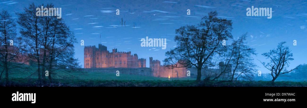 Reflexionen von Alnwick Castle und Bäume in den Gewässern des Flusses Aln, Northumberland, England. Stockbild