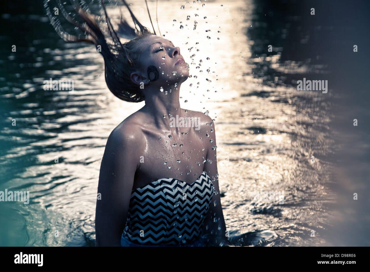 Frau, die Haare wieder in Gewässer zu werfen Stockbild