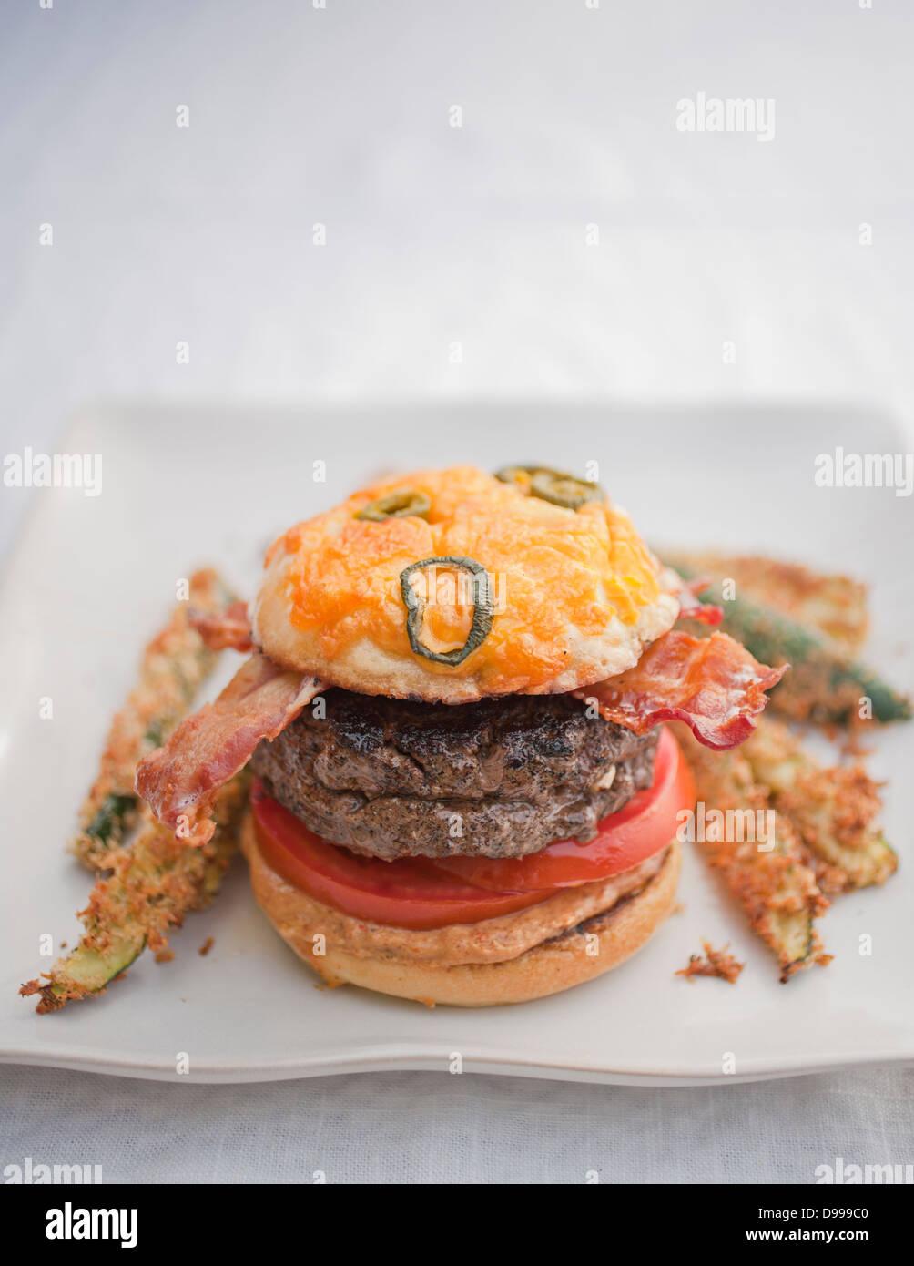 Burger Speck Tomaten Senf Jalapeño Käse Brötchen und Zucchini fries Stockbild