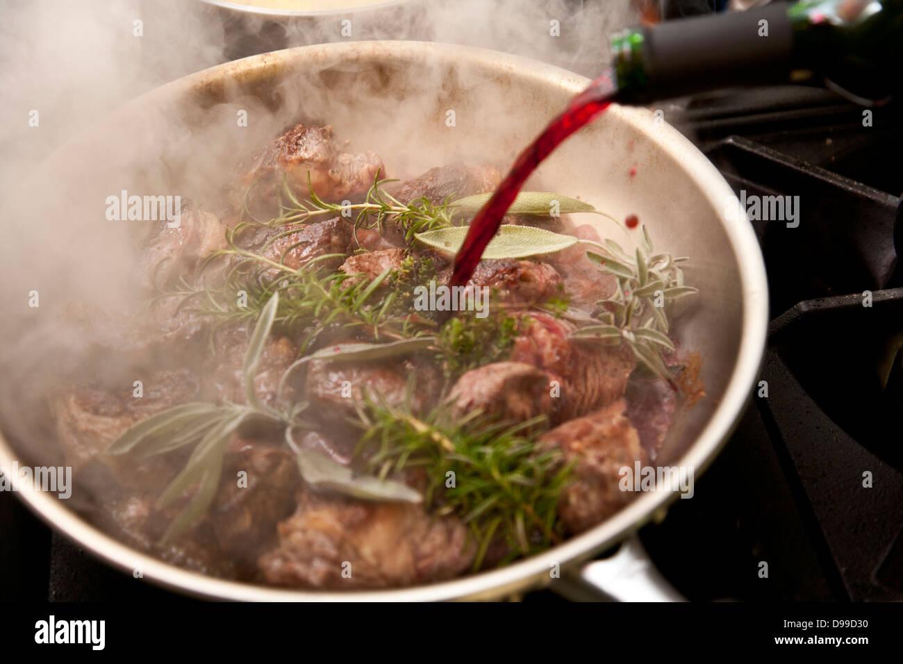 Geschmortes Fleisch in einer Pfanne mit frischen Kräutern und Rotwein Stockbild