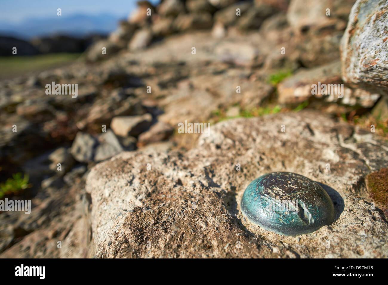 Ein Metall Nieten in einem Felsen auf einem Berggipfel Stockbild