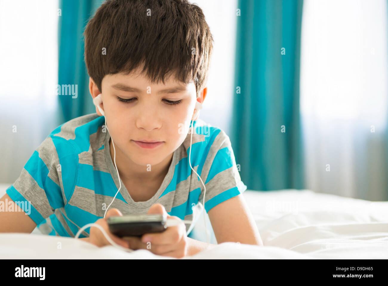 Junge, anhören von MP3-Player auf Bett Stockbild