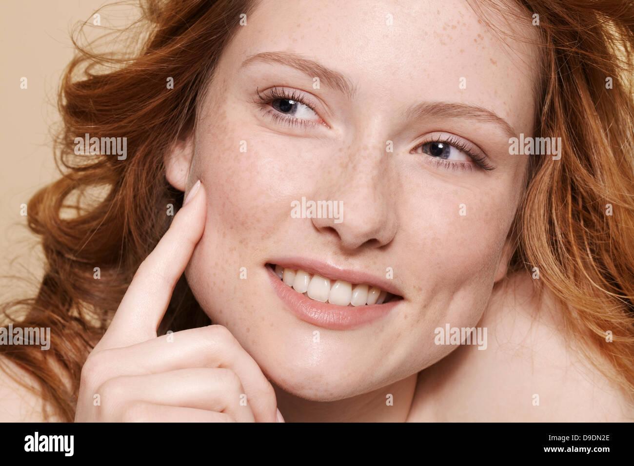 Studioaufnahme der jungen Frau mit lockigen roten Haaren, hand am Kinn zeigen Stockbild