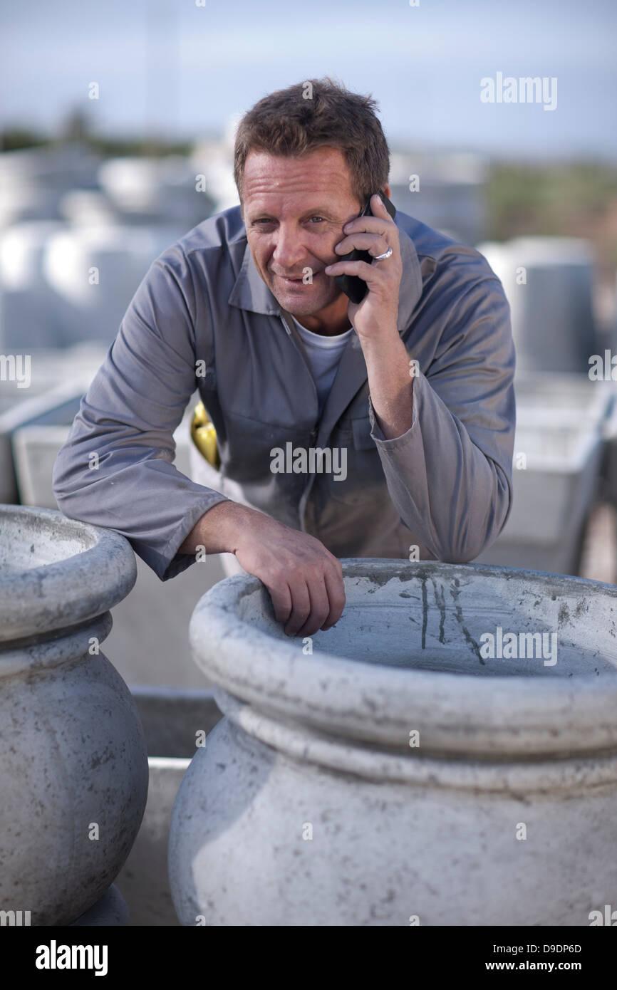 Fabrikarbeiter, am Handy sprechen Stockbild