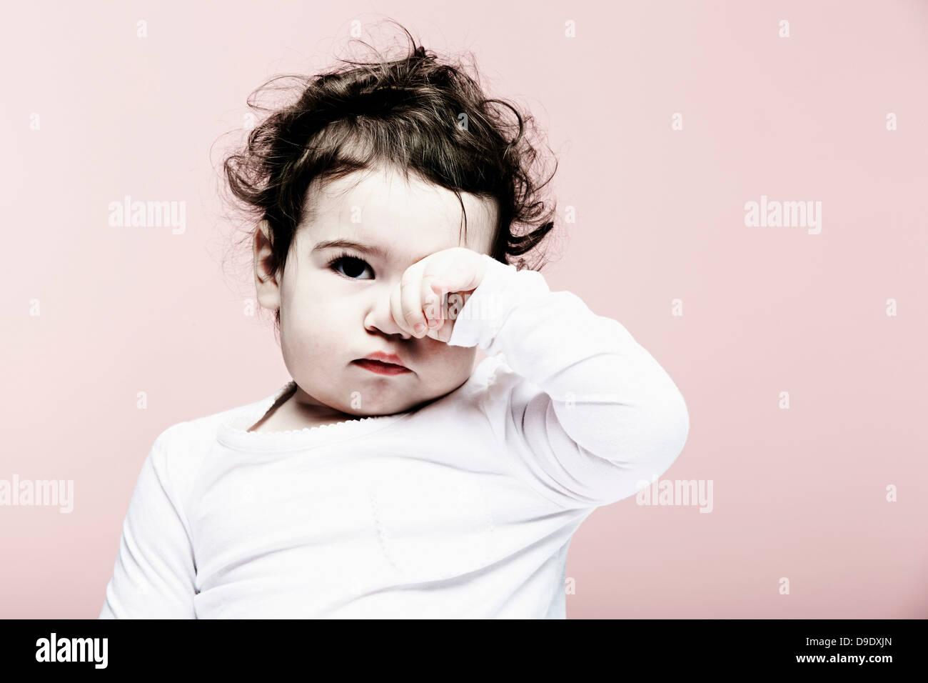 Porträt von Babymädchen Augen reiben Stockbild