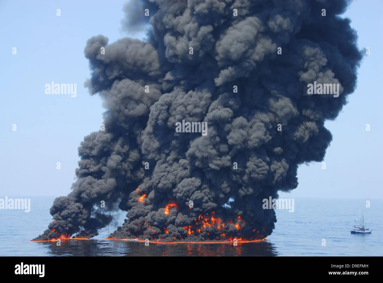 Dunkle Wolken von Rauch und Feuer entstehen, wie bei einem kontrollierten Brand in den Golf von Mexiko Öl verbrennt. Stockbild