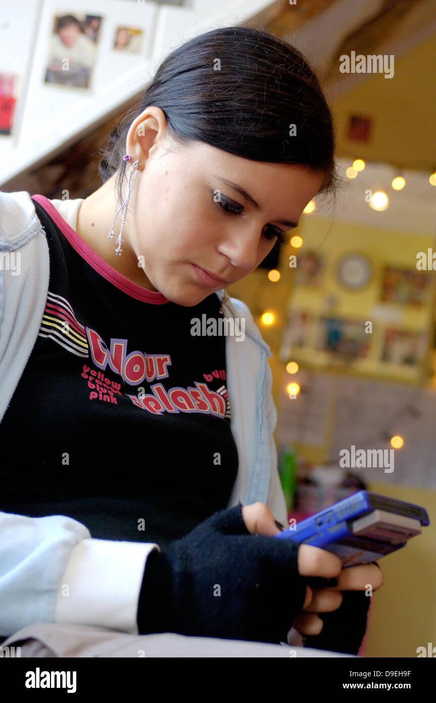 (Model Release) Jugendliche Mädchen spielt gameboy Stockfoto