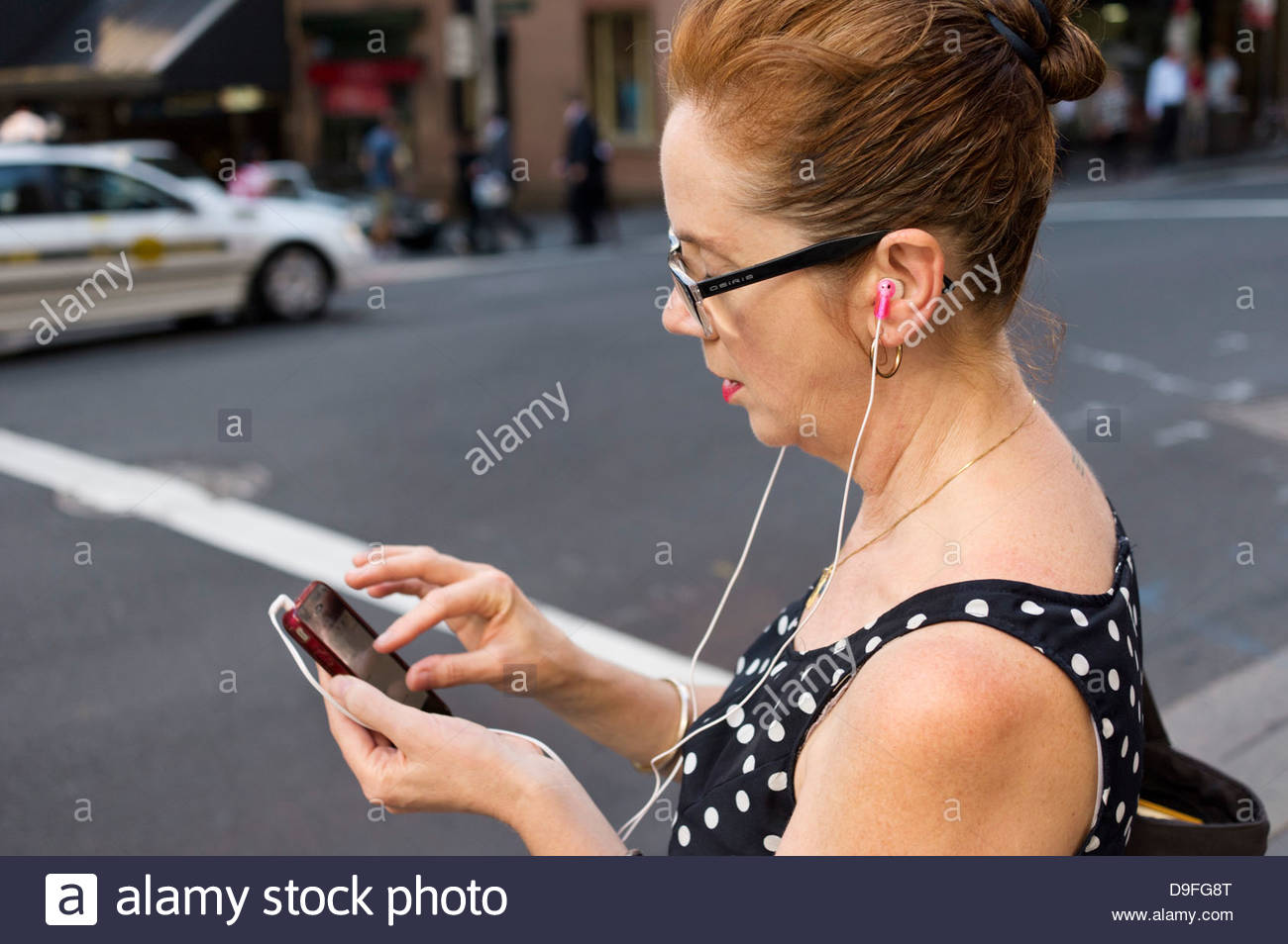 """Frau mit Smart-Phone macht """"Geste auf Touch-Screen, kneifen"""" beim hören über Kopfhörer; Stockbild"""