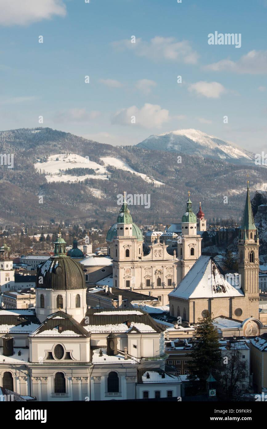 Die Kuppeln der Salzburger Dom und Franziskaner Kirche in der Altstadt und der Schnee bedeckt Berge, Salzburg, Österreich Stockbild