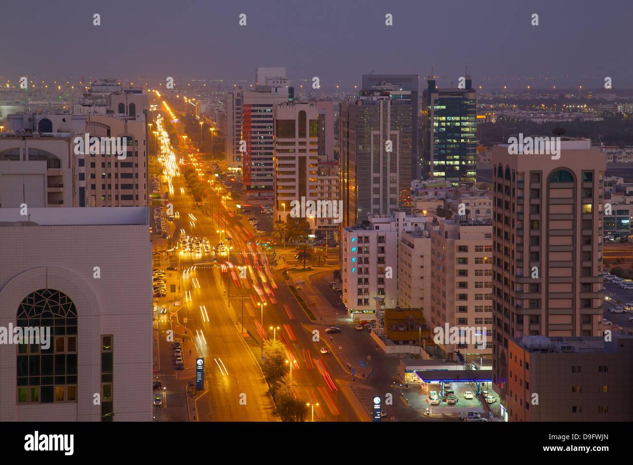 Skyline und Rashid Bin Saeed Al Maktoum Street bei Dämmerung, Abu Dhabi, Vereinigte Arabische Emirate, Naher Stockbild