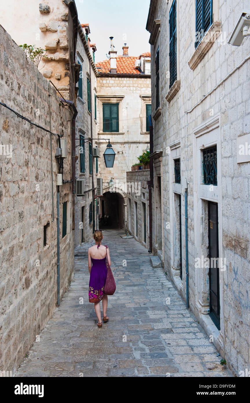 Altstadt von Dubrovnik, ein Tourist zu Fuß entlang einer schmalen Seitenstraße, Dubrovnik, Kroatien Stockbild