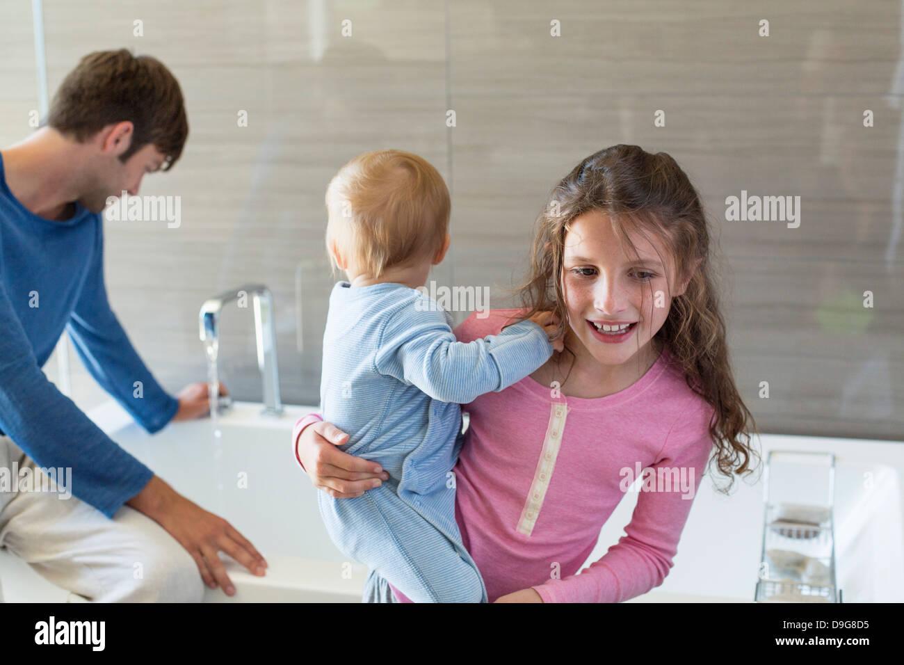 Mädchen lächelnd mit ihrem Bruder und ihrem Vater sitzt auf einem Wannenrand in einem Badezimmer Stockbild