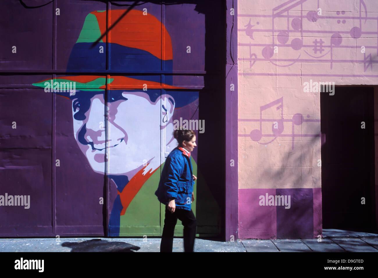 Eine Frau geht durch die Nachbarschaft der Abasto vor einem Plakat mit dem Bild von Carlos Gardel. Stockbild