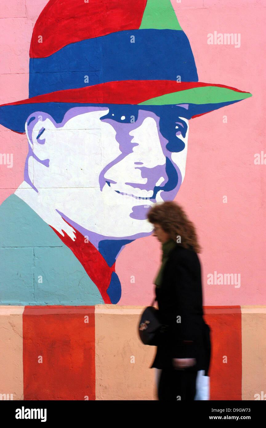 Eine Frau geht durch die Nachbarschaft der Abasto vor einem Plakat mit dem Bild von Carlos Gardel Stockbild