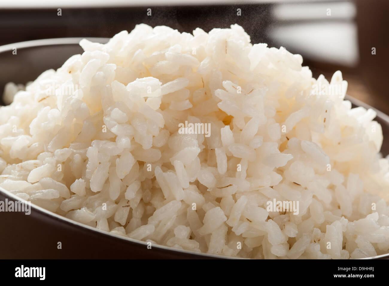 Schüssel mit Bio weisser Reis mit Stäbchen Stockbild