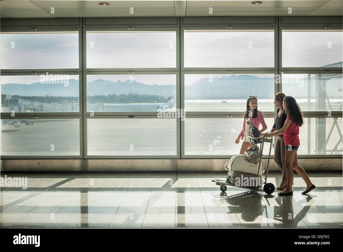 Mädchen im Teenageralter und Frau schieben Gepäckwagen am Flughafen Stockbild