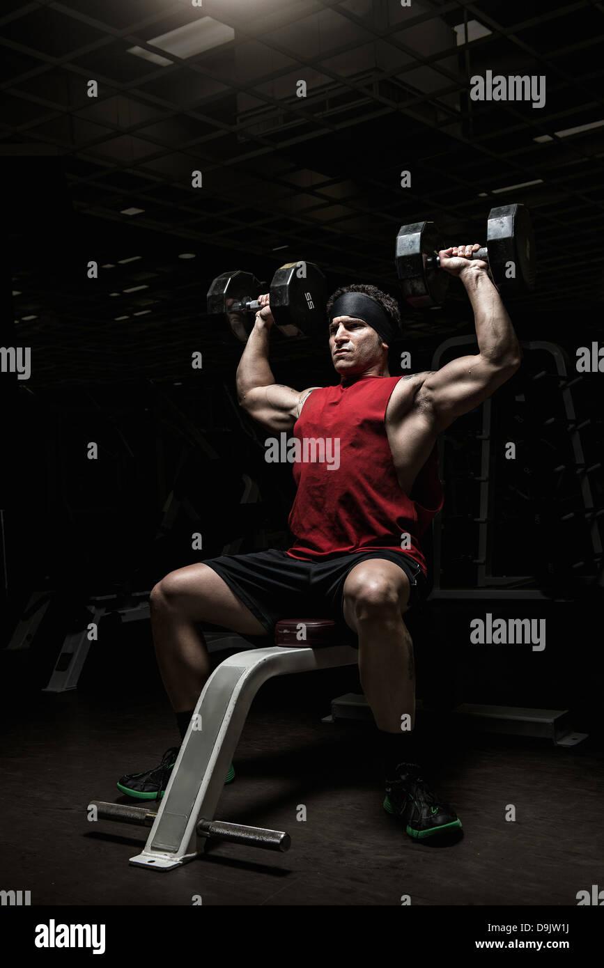 Muskulöser junger Mann Durchführung Schulter wirft mit Hanteln im Fitnessstudio Stockbild
