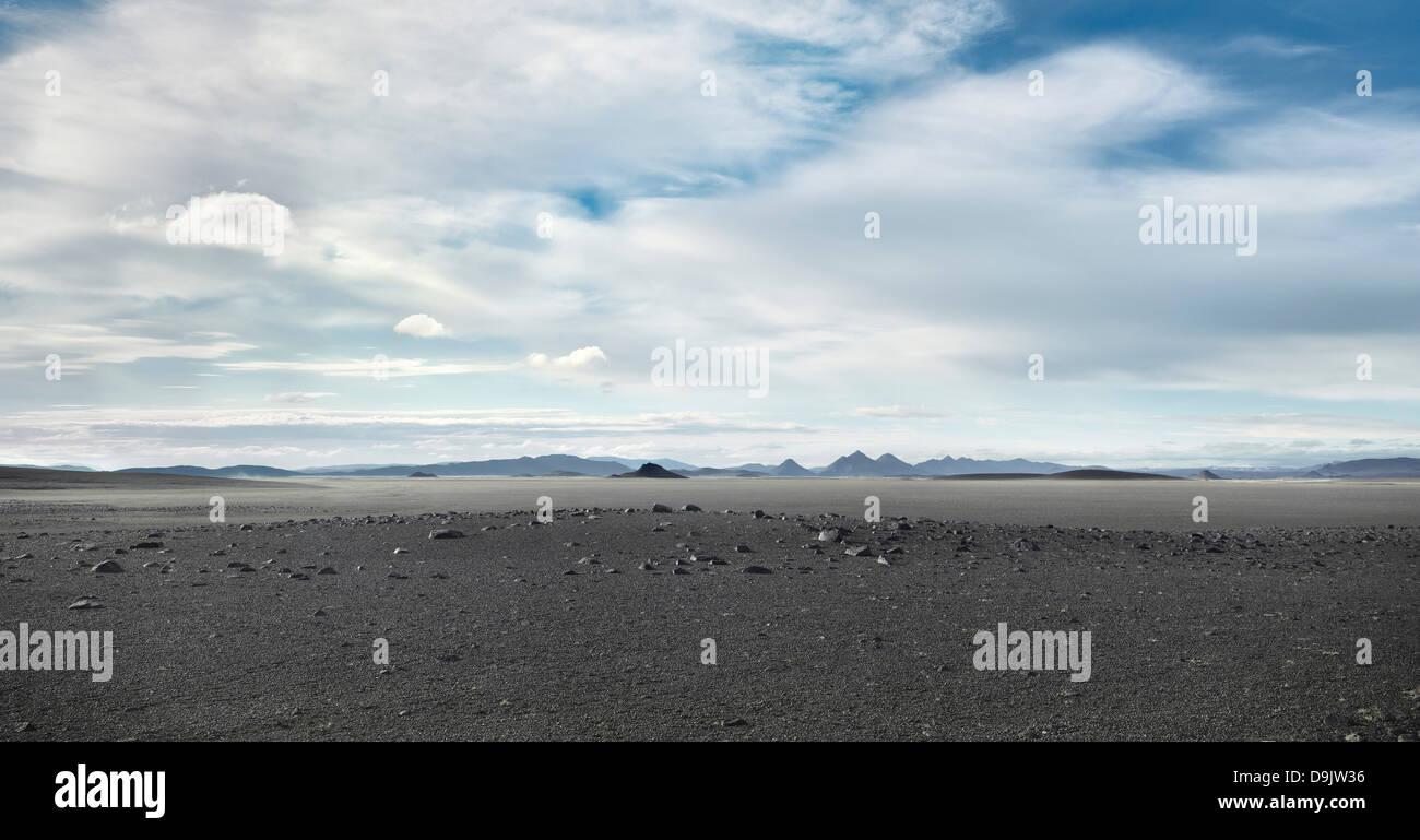 Graue karge Landschaft unter bewölktem Himmel Stockbild