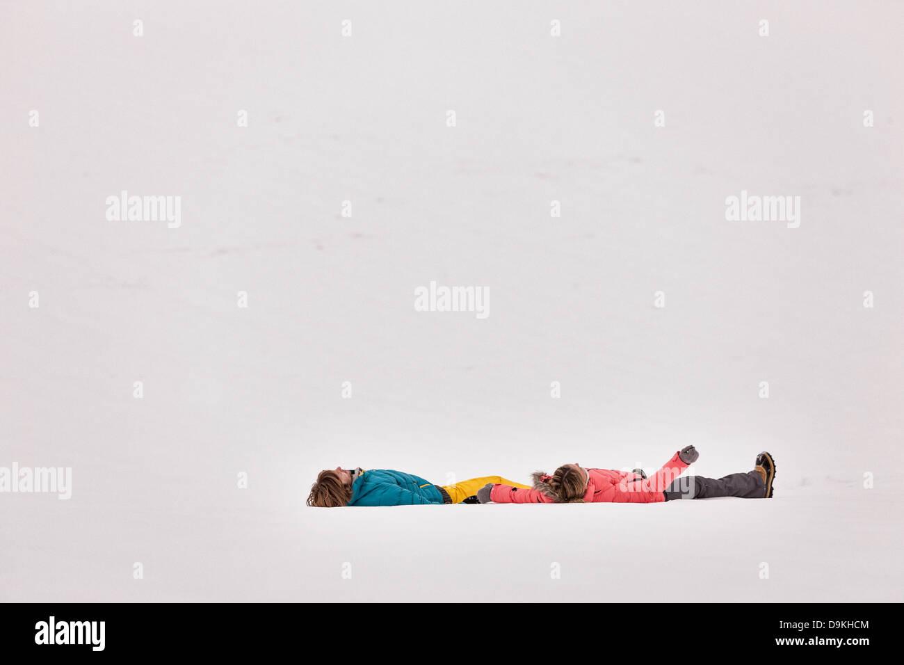 Paar am Rücken im Schnee liegen Stockbild