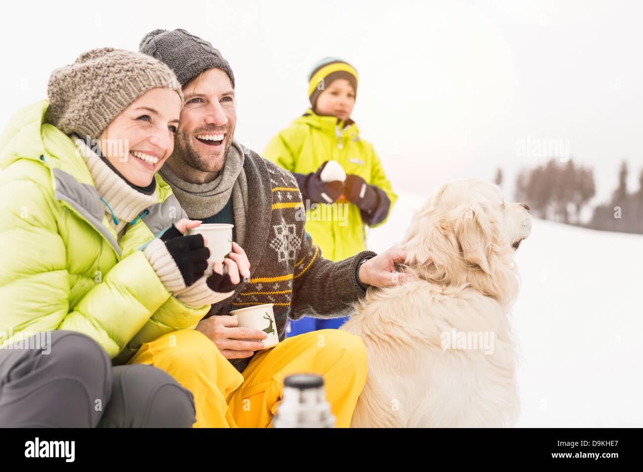 Mann und Frau mit heißen Getränken und Hund, Sohn im Hintergrund Stockbild