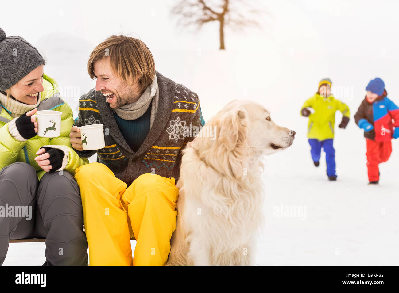 Mann und Frau mit heißen Getränken und Hund, Kinder im Hintergrund Stockbild