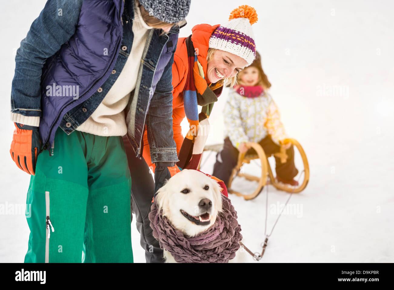 Mann und Frau mit Hund, Tochter im Hintergrund auf Schlitten Stockbild