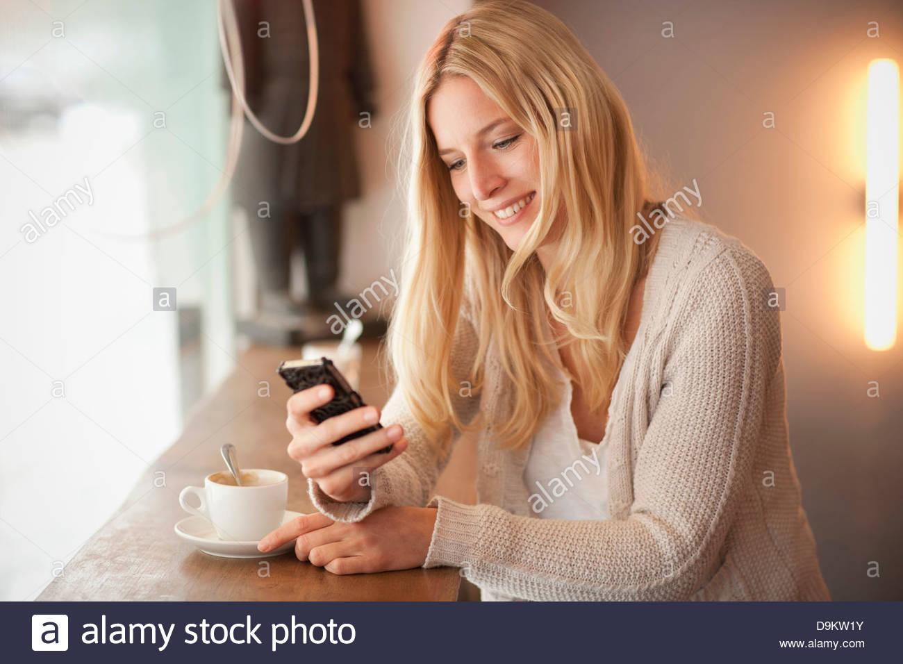 Junge Frau mit Handy im café Stockbild